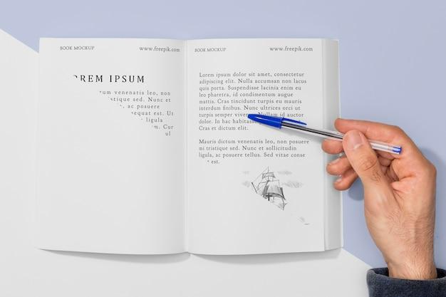 펼친 책 모형 위에 펜을 들고 상위 뷰 손 무료 PSD 파일