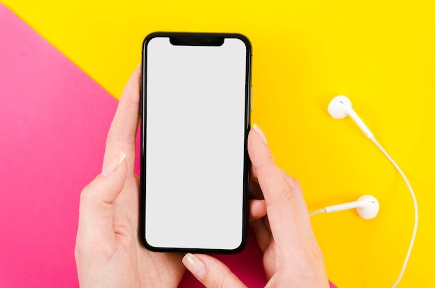 Top view hands holding smartphone mock-up with earphones Free Psd