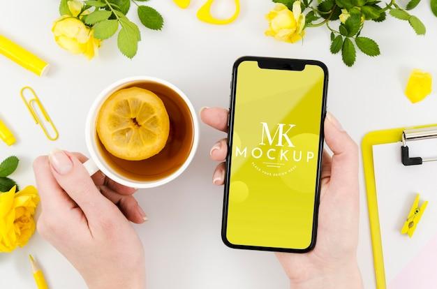 紅茶とスマートフォンのモックアップを保持している平面図手 無料 Psd