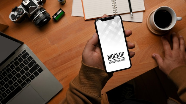 Top view of male hand holding smartphone mockup on worktable Premium Psd
