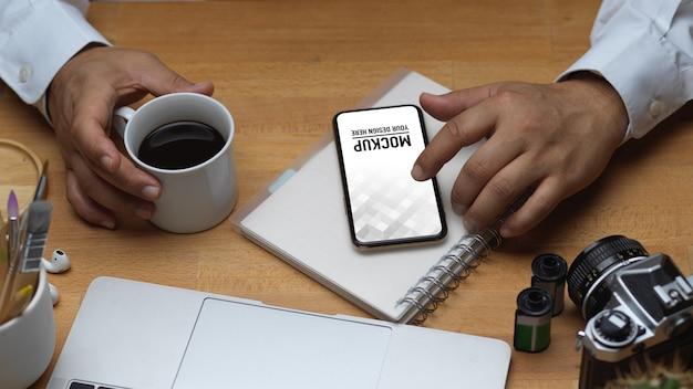 Top view of male hand using smartphone and holding coffee mug on workspace Premium Psd
