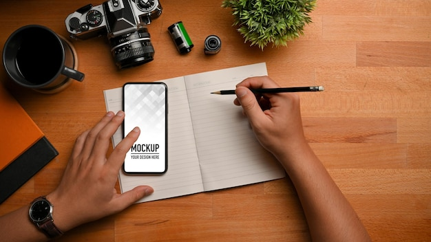 Top view of male hand writing on blank notebook while using smartphone mockup Premium Psd