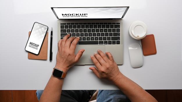 Top view of male hands typing on laptop keyboard mockup Premium Psd