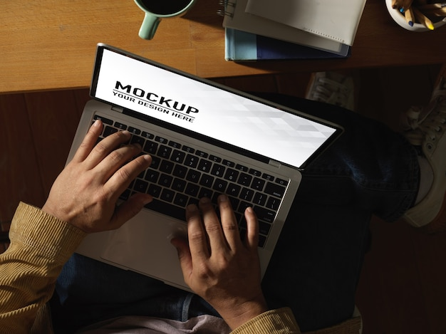 Top view of male hands typing on laptop mockup Premium Psd