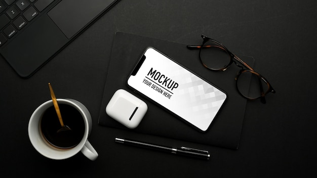 Top view of mockup smartphone on black table with accessories Premium Psd