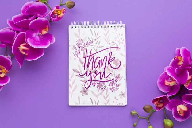 Top view of notebook and flowers on purple background Free Psd