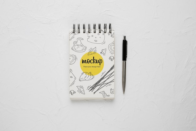 Top view of notebook with cheese design and pen Free Psd