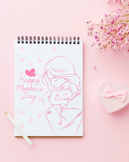 Top view of notebook with flowers and present Free Psd