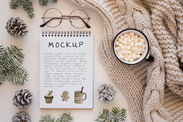 Top view of notebook with marshmallows and pine cones Free Psd