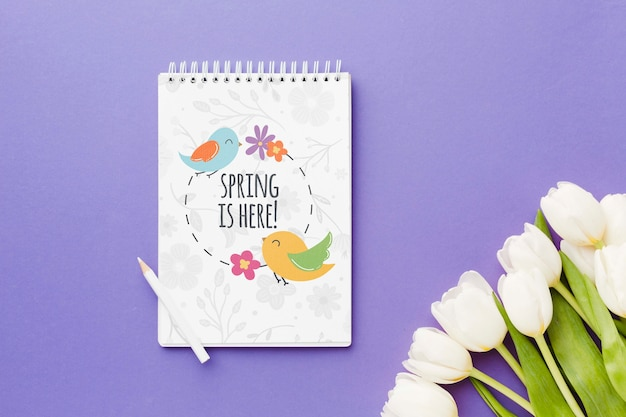 Top view of notebook with spring tulips Free Psd