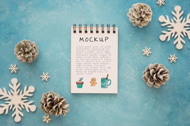 Top view of notepad with pine cones and snowflakes Premium Psd