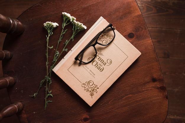 花とグラスが付いている椅子の上の本のトップビュー 無料 Psd