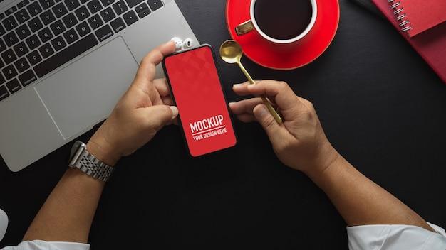 Вид сверху бизнесмена, держащего макет экрана смартфона и кофе Premium Psd