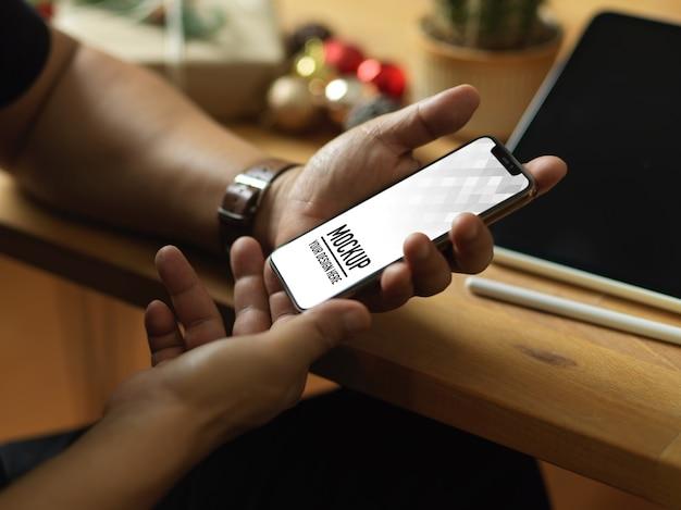 スマートフォンのモックアップとクリスマスの装飾を持っている手の上面図 Premium Psd