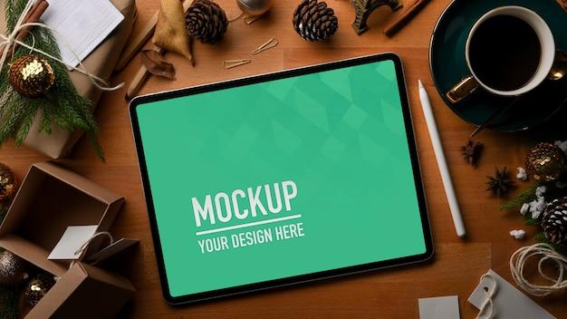 コーヒーカップとクリスマスの装飾が施されたモックアップタブレットの上面図 Premium Psd