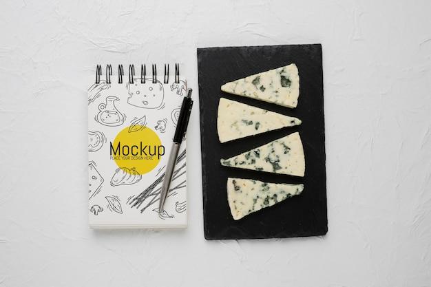 Вид сверху блокнота и ручки с заплесневелым сыром Бесплатные Psd