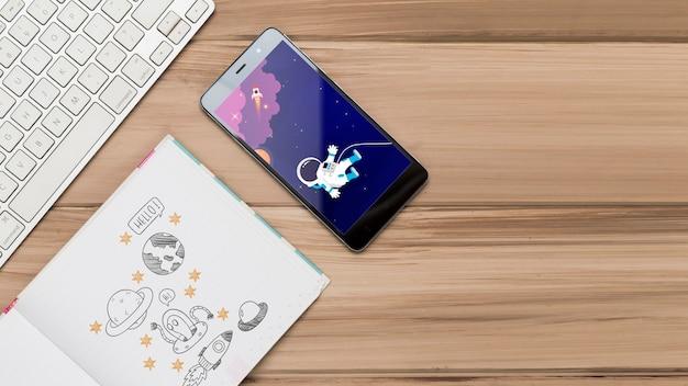 Вид сверху смартфона с клавиатурой и рисунками Бесплатные Psd