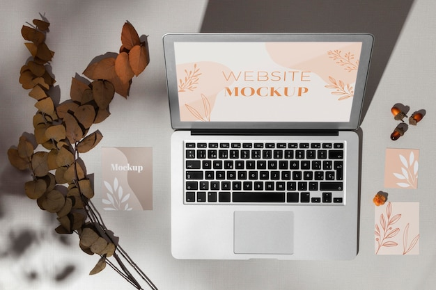 Top view opened laptop with screen mockup next to leaves Free Psd
