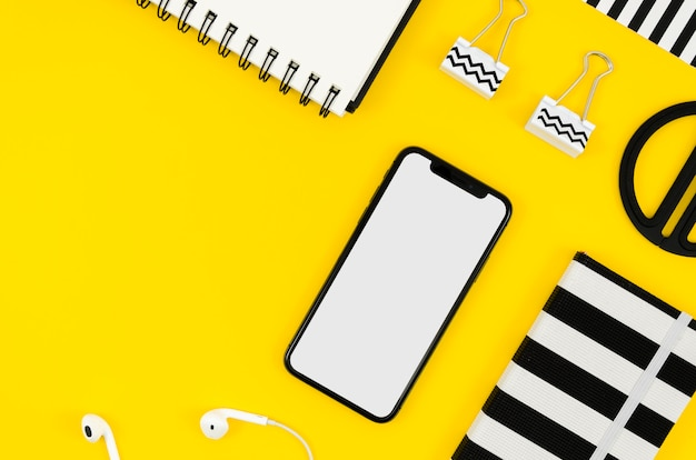 Top view phone mock-up with notepad and earphones Free Psd