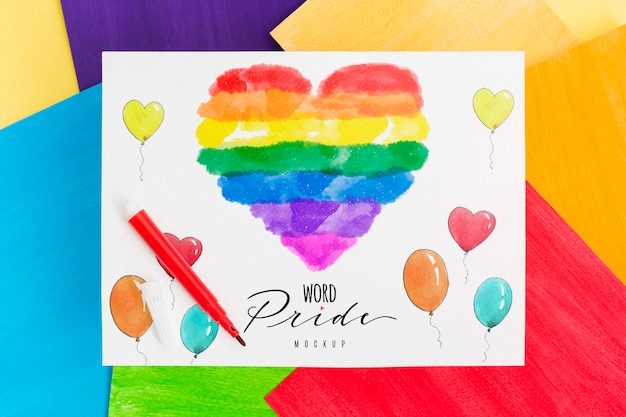 Top view of rainbow colored heart on paper with balloons for lgbt pride Free Psd