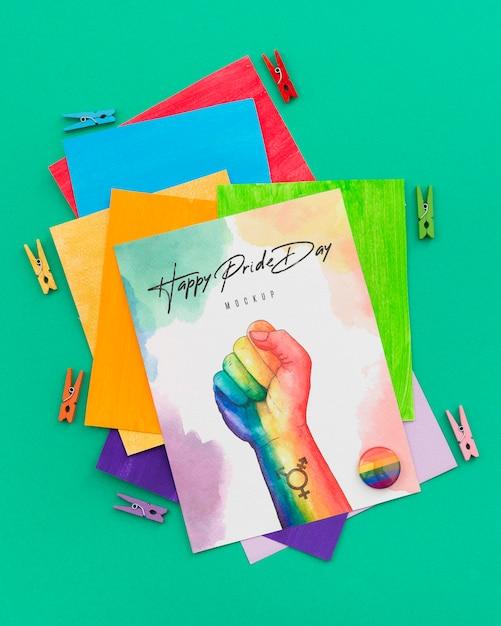 Vista dall'alto di carte colorate arcobaleno con spille e pugno per orgoglio lgbt Psd Gratuite