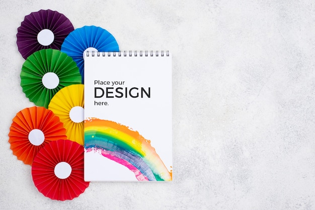 Top view of rainbow colored rosettes and notebook Free Psd