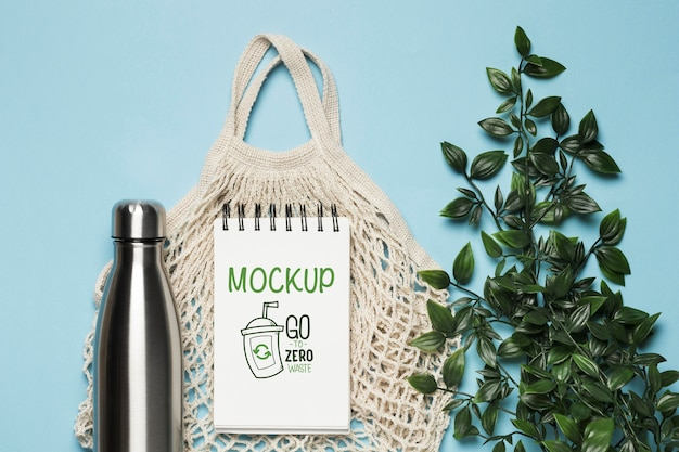 Top view of reusable bag with plant and bottle Free Psd