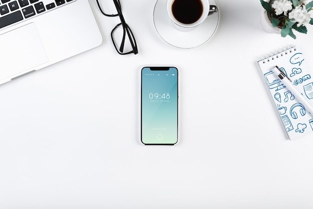 Top view smartphone mockup on workspace Free Psd