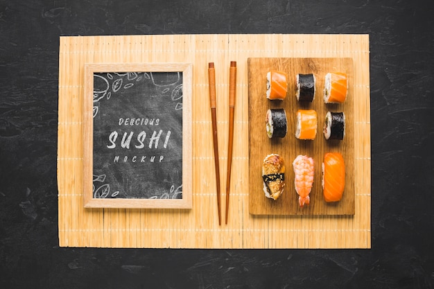 Top view of sushi on chopping board with chopsticks and blackboard Free Psd