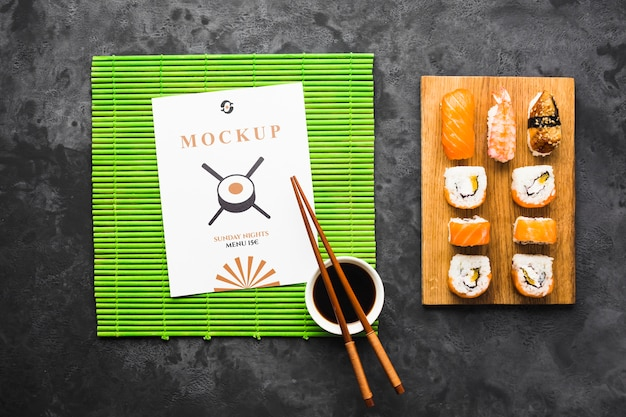 Top view of sushi on chopping board with chopsticks and soy sauce Free Psd