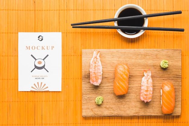Top view of sushi on chopping board with soy sauce and chopsticks Free Psd