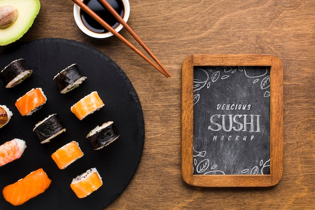 Top view of sushi variety with blackboard and soy sauce Premium Psd