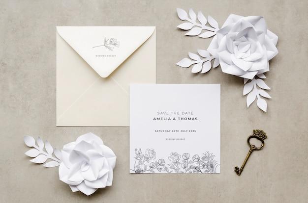 Vista superiore della partecipazione di nozze con rose e chiave di carta Psd Gratuite