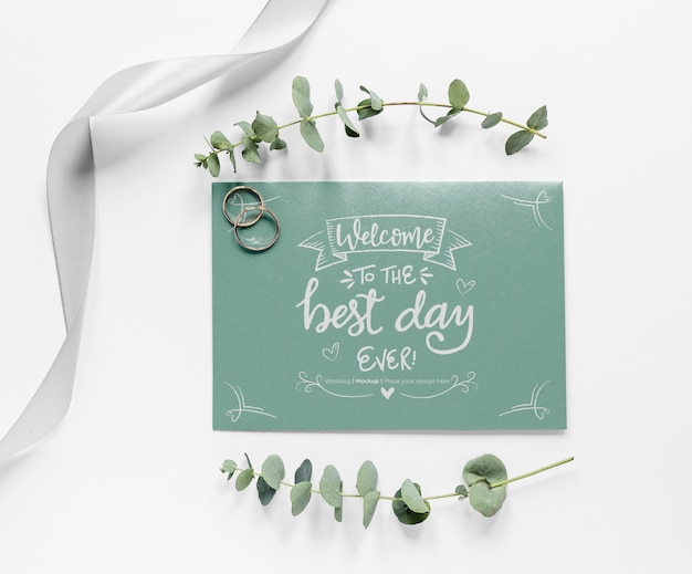 Top view of wedding card with plants and rings Free Psd