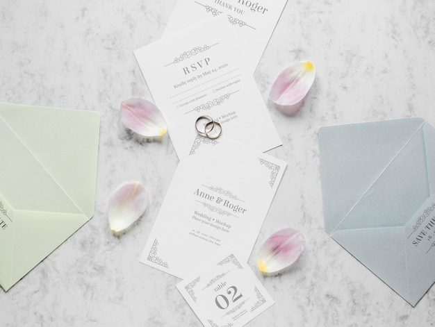Top view of wedding cards with rings and flower petals Free Psd