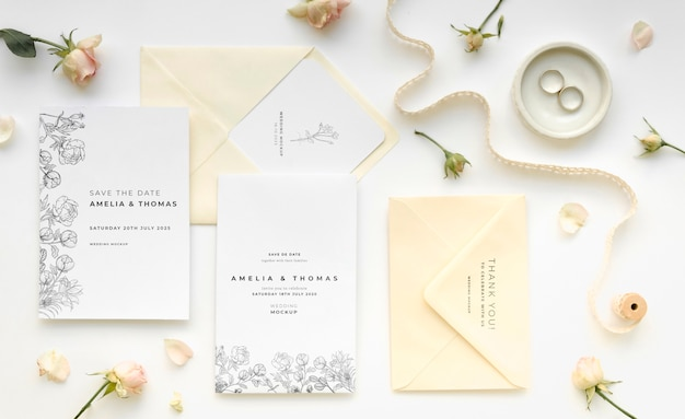 Top view of wedding cards with rings and flowers Free Psd
