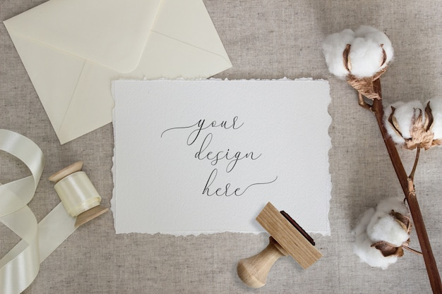 Torn edge paper card on linen cloth with cotton flowers and silk ribbon. wedding stationery mockup. invitation Premium Psd