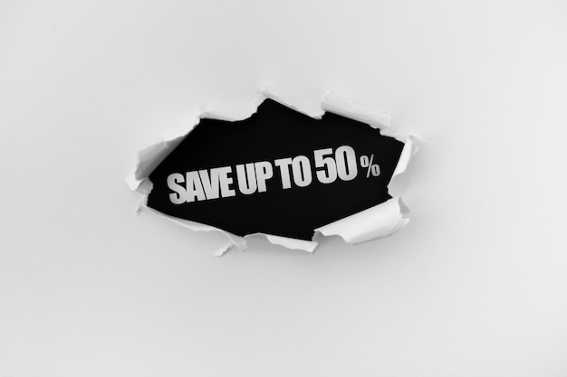 Torn hole in the white wall of paper on a black background Free Psd