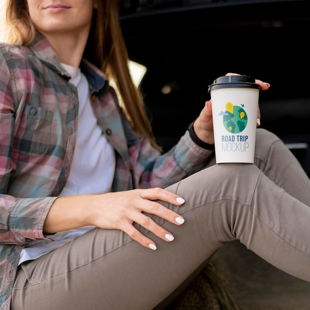 Traveler holding a mock-up cup of coffee Free Psd