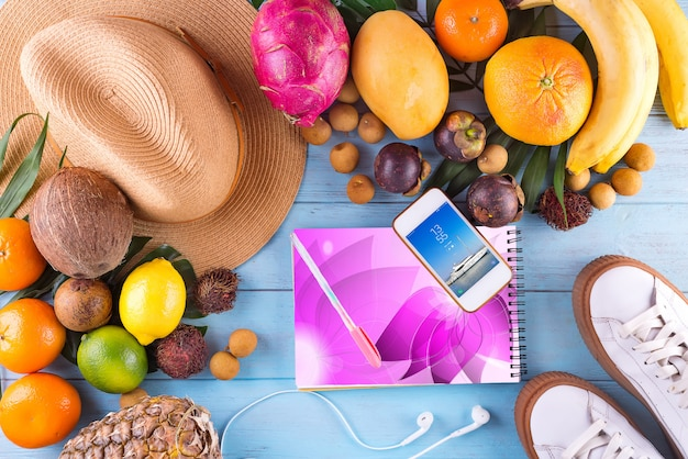Tropical hat, many fruits on blue wooden background Premium Psd