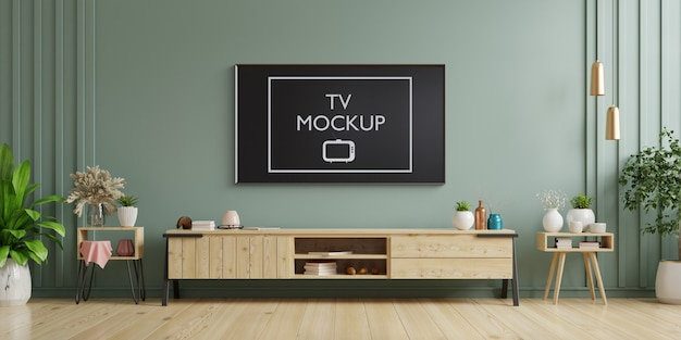 Tv on cabinet in modern living room with armchair, lamp, table, flower and plant on dark green wall. 3d rendering Premium Psd