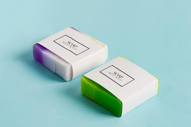 Два мыла ручной работы обернуть коробку макет пакета с красочными мыло бар, изолированных на синем фоне Premium Psd