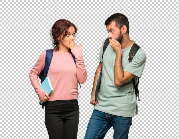 Two students with backpacks and books covering mouth with hands for saying something inappropriate Premium Psd