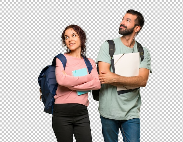 Two students with backpacks and books looking up while smiling Premium Psd