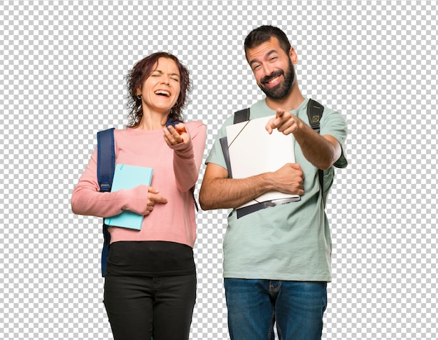 Two students with backpacks and books pointing with finger at someone and laughing a lot Premium Psd