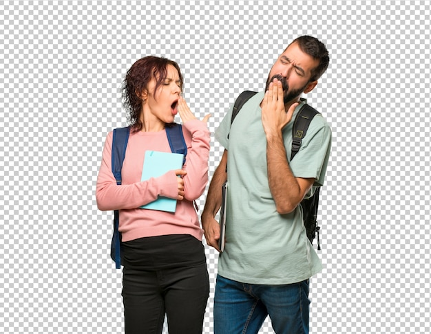 Two students with backpacks and books yawning and covering mouth with hand Premium Psd