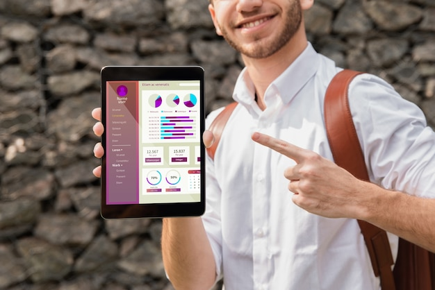 University man holding and pointing at tablet Free Psd