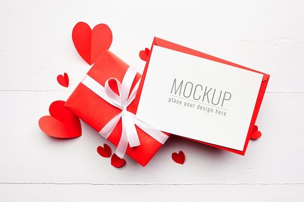Макет карты дня святого валентина с подарочной коробкой и сердечками из красной бумаги Premium Psd
