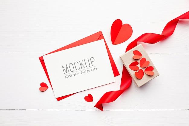 선물 상자, 빨간 리본 및 종이 하트 발렌타인 카드 모형 프리미엄 PSD 파일