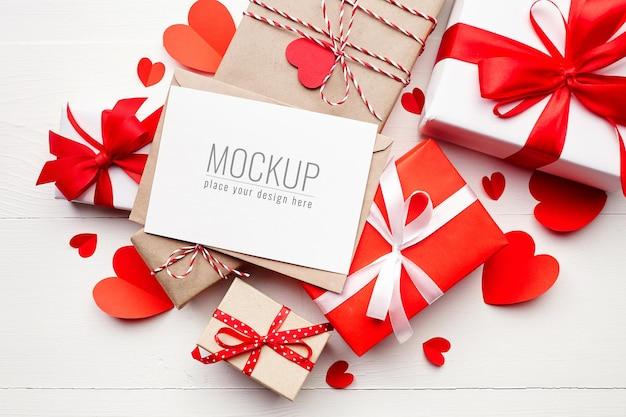 Макет карты дня святого валентина с подарочными коробками и красными бумажными сердечками Premium Psd